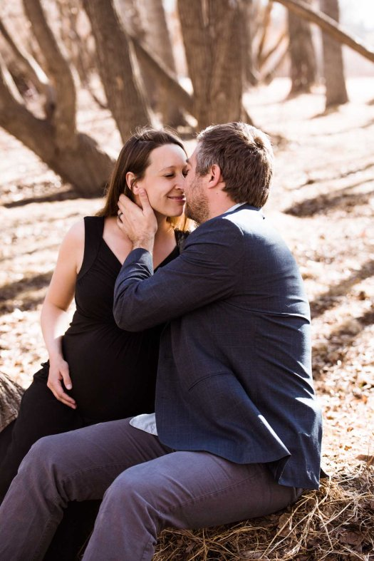 Calgary lifestyle photographer, maternity photos at Confederation Park, couple in front of trees
