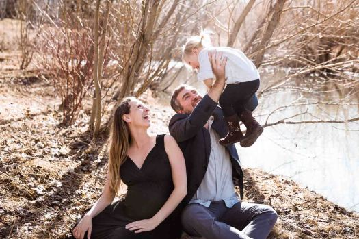 Calgary lifestyle photographer, maternity photos at Confederation Park, family in front of trees