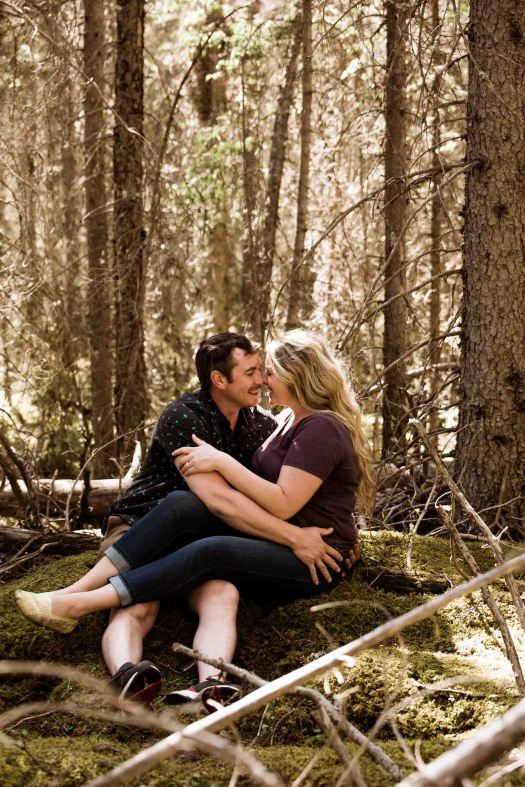 Calgary wedding photographer, engagement photos in a beautiful mountain location, couple sitting in moss