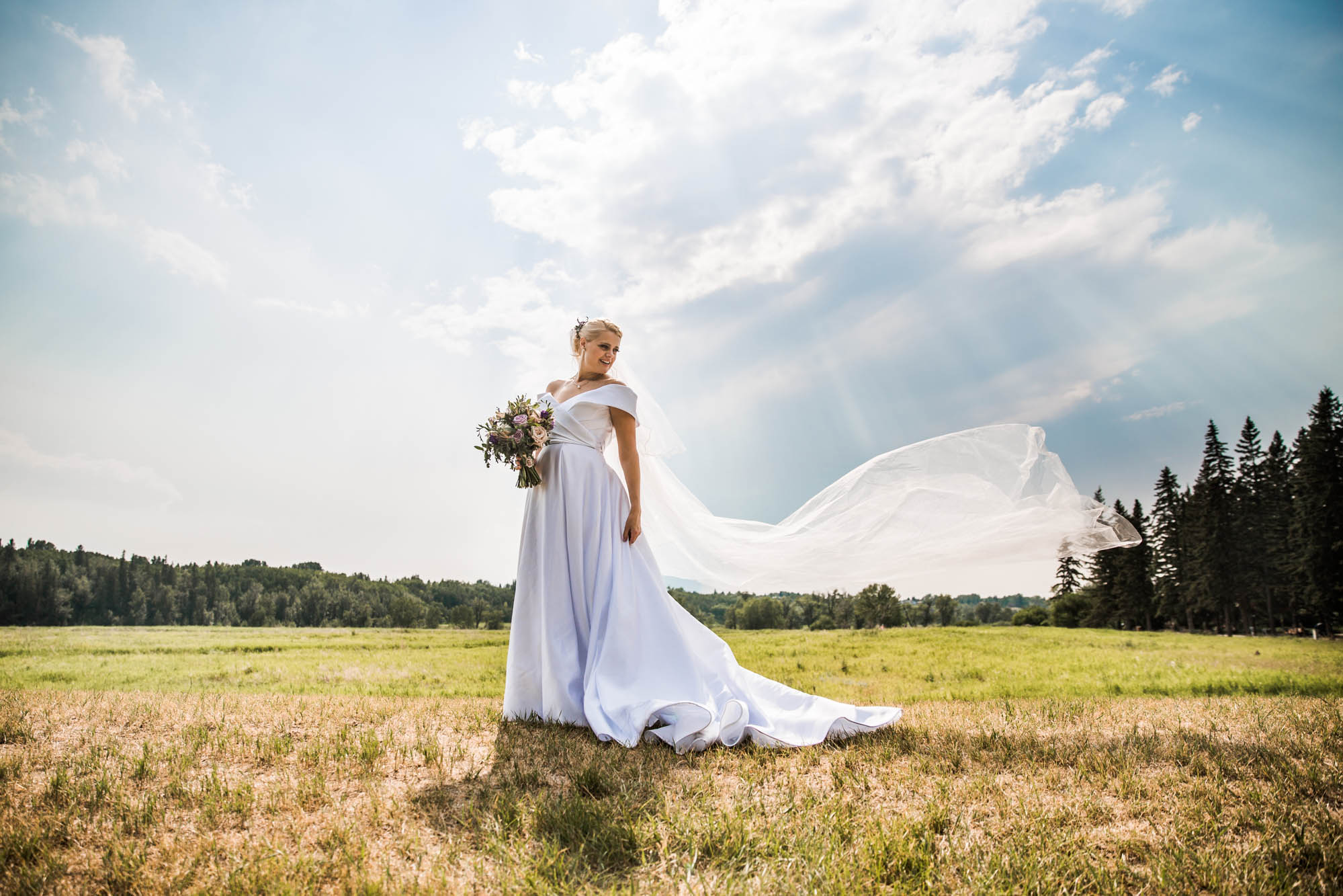 Calgary wedding and family photographer, bride in front of beautiful sky at Fish Creek Park in Calgary