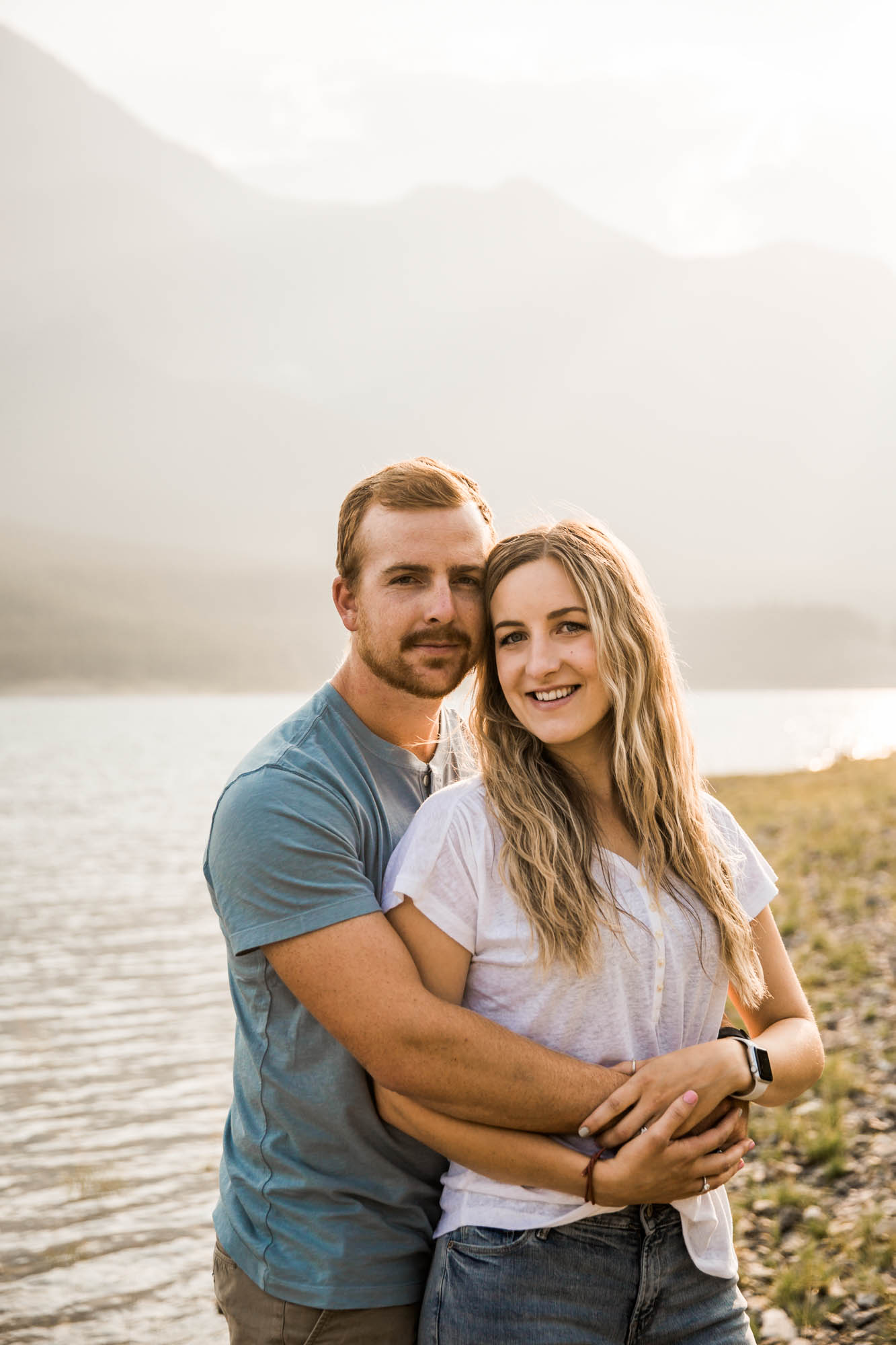 Calgary wedding and engagement photographer, couple by the water and mountains at sunset in Kananaskis Country