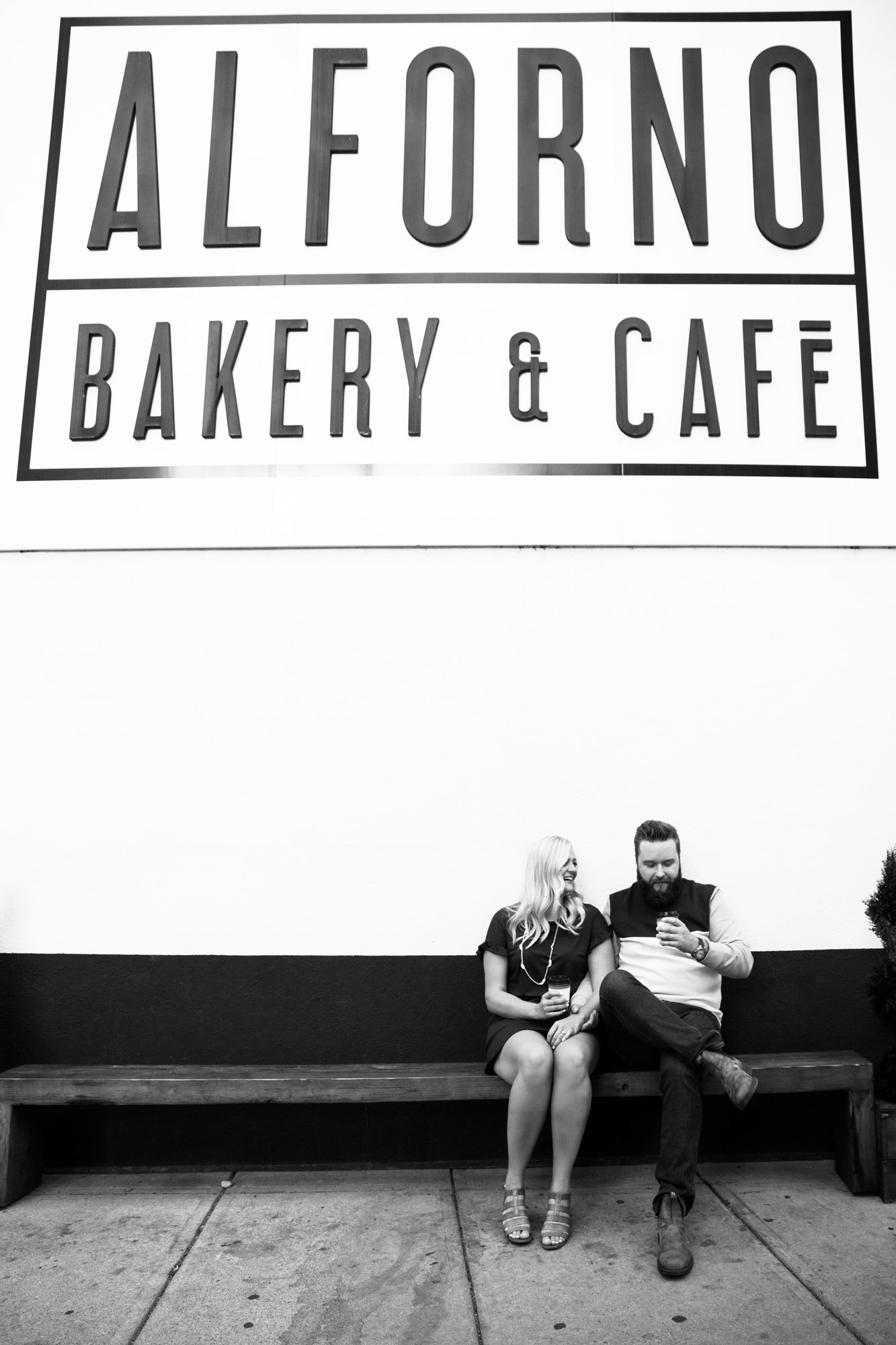 Calgary wedding photographer, engagement photos at Alforno Bakery and Cafe, couple sitting on a bench outside