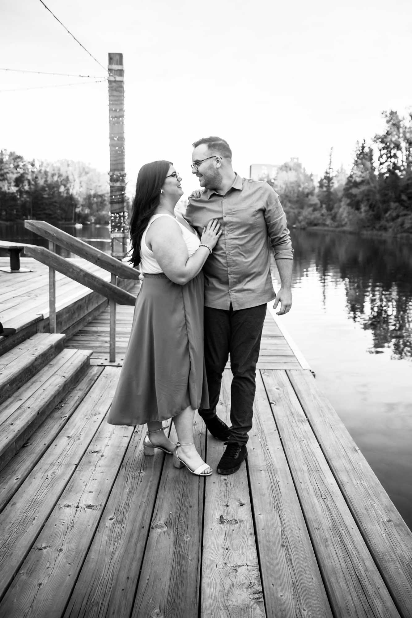 Calgary wedding photographer, engagement photos at Bowness Park, couple in front of the water and a beautiful orange sunset